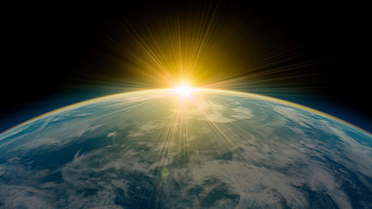 Jordklotet sett från rymden. Solen skymtar precis bakom.