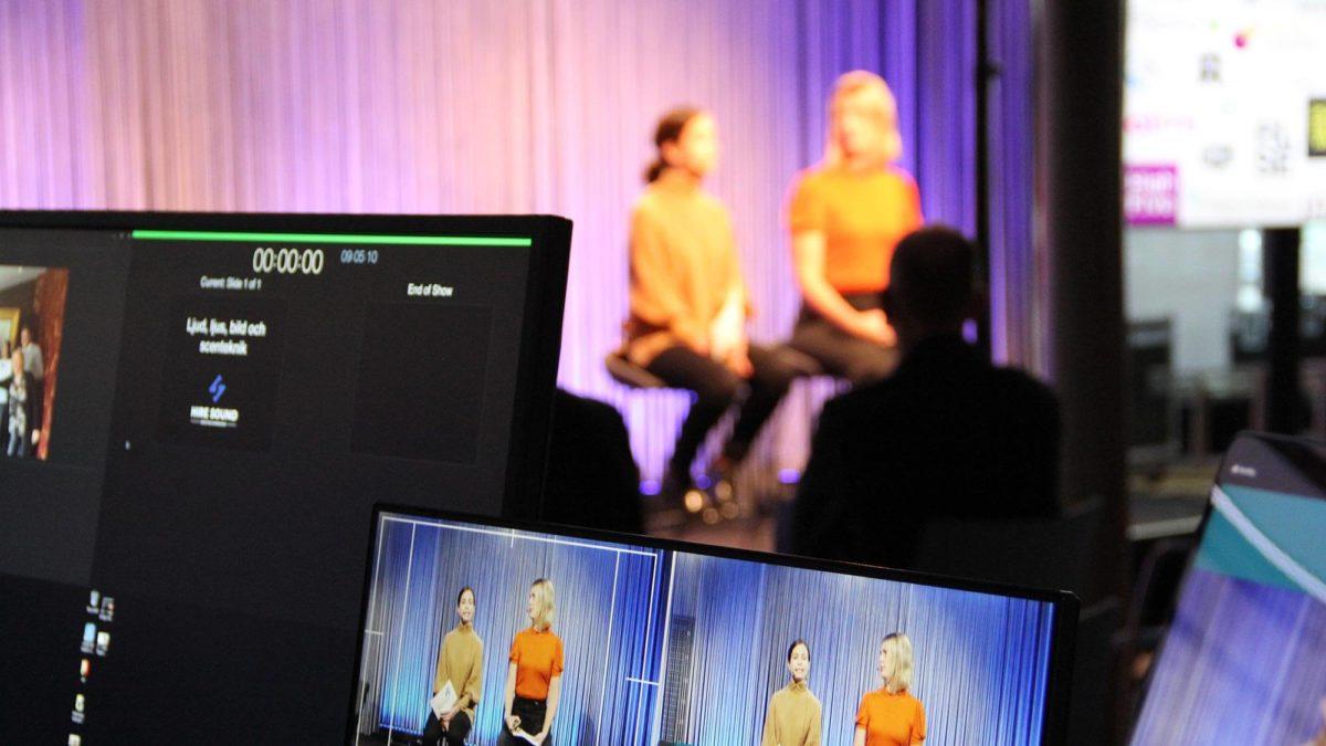 Fokus på flera datorskärmar som sköter inspelningen av Halland Tech Week 2020. Just nu filmas två personer som sitter och pratar på scenen i bakgrunden.