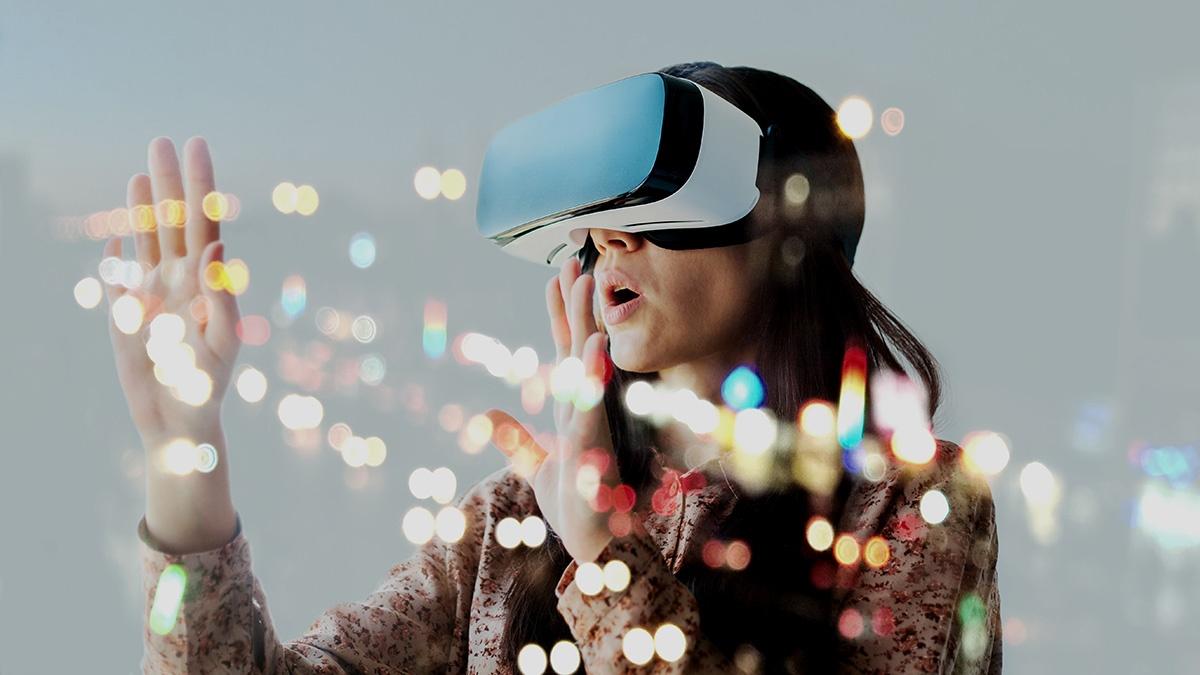 Person har ett VR-headset på sig och håller chockat händerna framför sig i tomma luften.